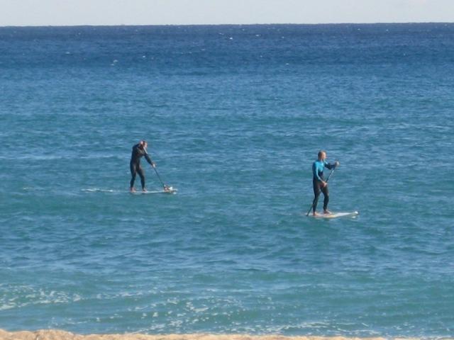 Dos practicantes de actividades náuticas en la playa de la Barceloneta.